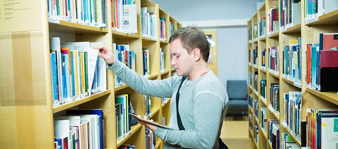Student between shelves in TUAS library